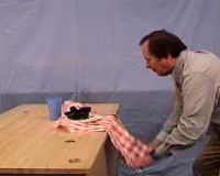 Professor pulling tablecloth from beneath plate and cup.