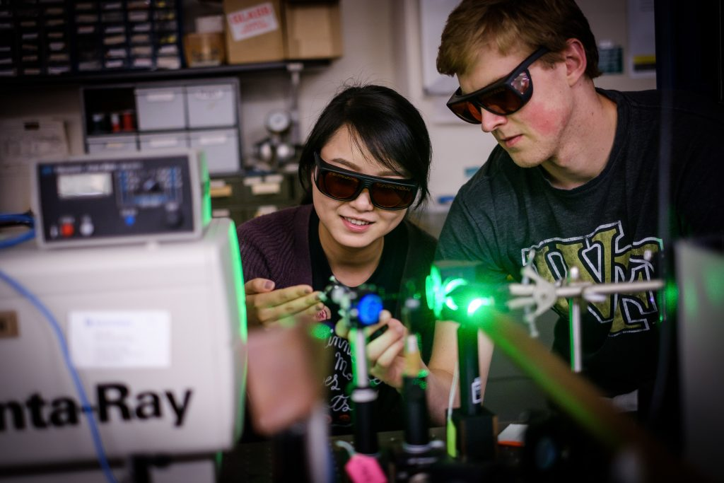 Wake Forest physics graduate students Peiyun Li and Drew Onken work with a sapphire laser to study crystals that can detect gamma rays, in Prof. William's lab in Olin Physical Laboratory on Tuesday, July 11, 2017.