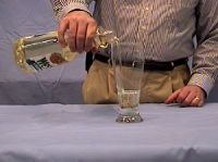 Pouring cooking oil into a beaker containing a Pyrex rod