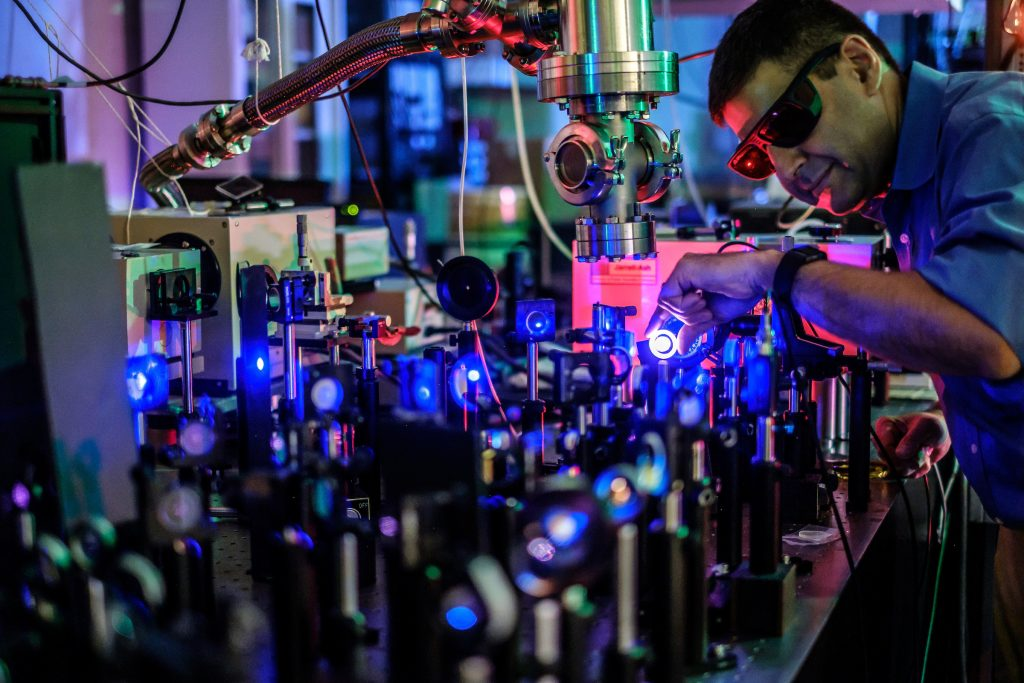 Wake Forest research professor Burak Ucer works with a sapphire laser to study crystals that can detect gamma radiation, in his lab in Olin